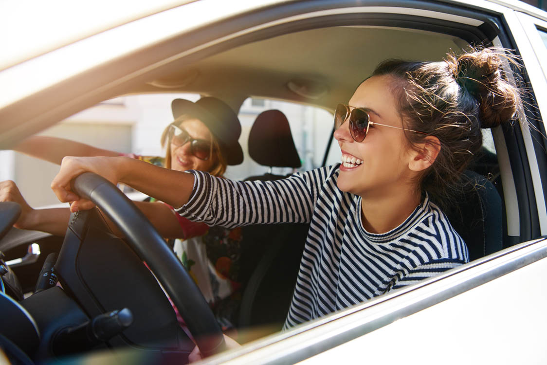 Ladies with white teeth smile in car