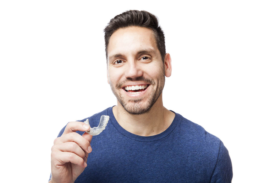 Man with Invisalign in hand